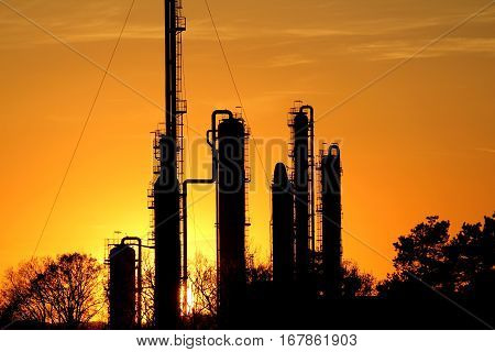silhouette of oil refinery against the sun