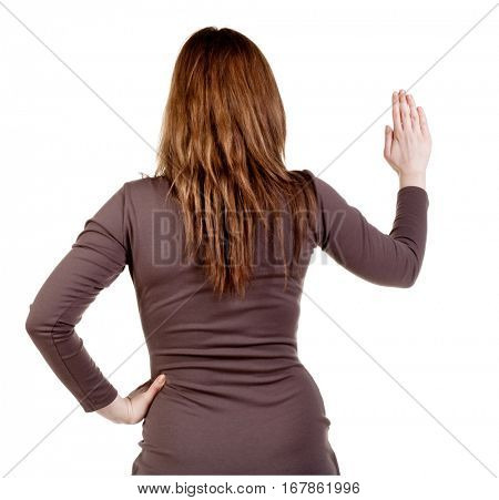 back view of Businesswoman . Young bisiness woman in dress presses down on something. Isolated over white background. Rear view people collection. backside view of person.