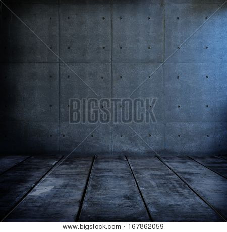 Dark black room with bluish light. Dark concrete wall and floor.