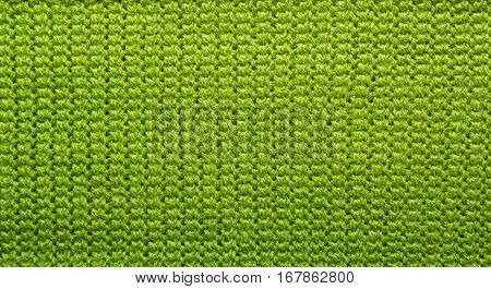 Knitted green background. Green knitted wool texture. Tunisian crochet. Tunisian pattern. Seamless background. Hand-knitted. Wrong side
