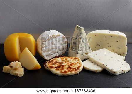 Collection of cheeses on a slate cutting board against gray background