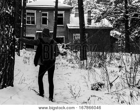 Man near the old house in winter forest
