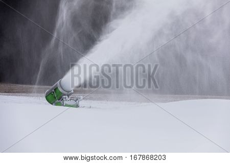 Making snow on the ski track. Artificial snow in the ski resort. Snow machine spews snow.