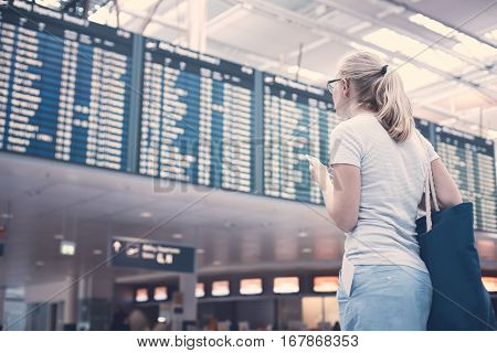 Young blonde woman with phone in her hand, tickets in pocket of skirt and shoulder bag checking flight timetable in international airport - travel concept
