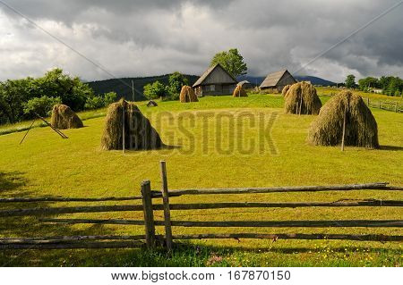 Field with haystack on mountains meadow. Fabulous Carpathians