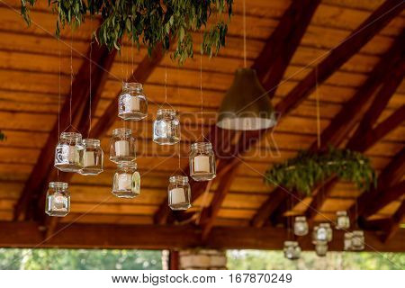 white candles in glass jars hanging from the ceiling