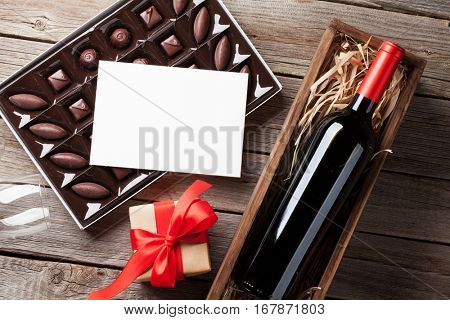 Valentines day greeting card. Red wine, gift box and chocolate box on wooden table. Top view with space for your greetings