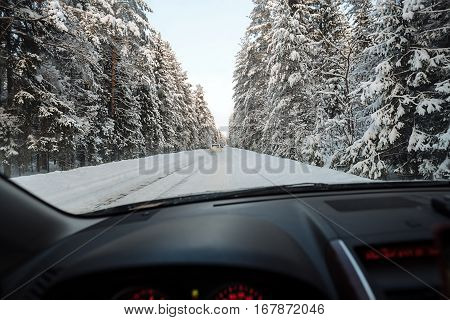 Passenger black car moving on winter road among deep forest shot from the driver s seat