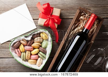 Valentines day greeting card. Red wine, macaroons gift box and glasses on wooden table. Top view with space for your greetings