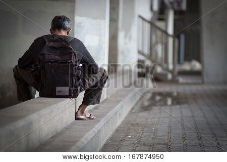 Homeless people sit on concrete floor under the bridge pedestrian area.