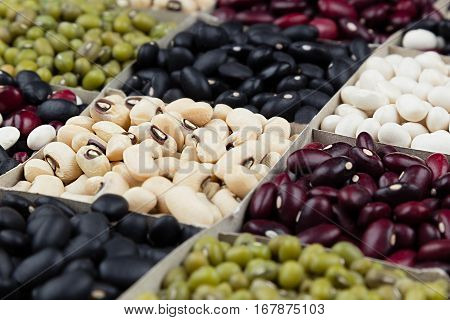 Kidney beans background assortment haricot - red black white mung in square cells macro. Healthy protein food.