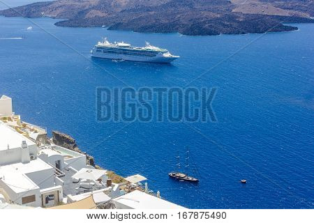 View on the mediterranean sea, caldera and volcano. Traditional white architecture of Santorini island, Thira, Greece. Cruise ship in blue sea.