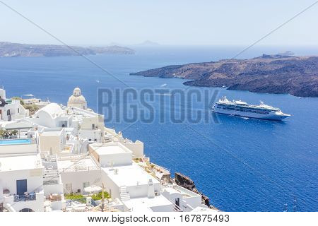 Beautiful panoramic view on the mediterranean sea, caldera and volcano. Traditional white architecture of Santorini island, Thira, Greece. Cruise ship in blue sea.