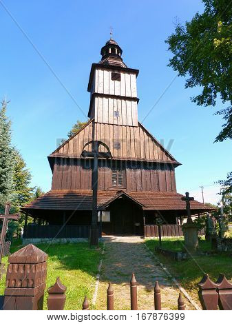 Photo of a small wooden church under a blue sky