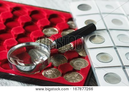 Different collector's coins in the box for coins and a magnifying glass soft focus background