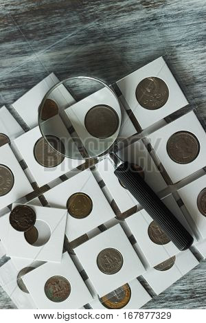 Page with collector's coins in the pockets and a magnifying glass wooden background