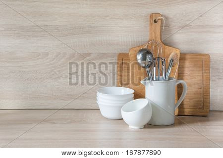Crockery tableware utensils and other different stuff on wooden table-top. Kitchen still life as background for design. Image with copy space.