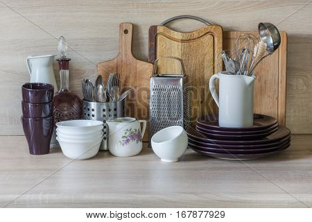 Crockery tableware utensils and other different stuff on wooden table-top.Kitchen still life as background for design. Image with copy space.