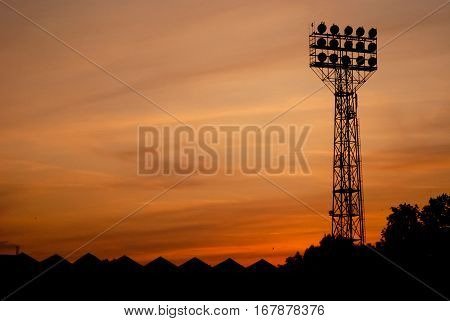 Stadium floodlights on a sports field at night with red sky