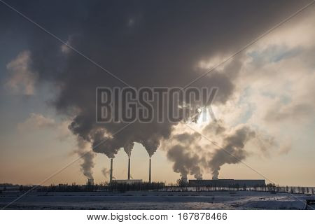 Silhouette of coal plant with gray smoke. Environment pollution by power plants. Perfect industrial background. Free space for text on gray smoke background.
