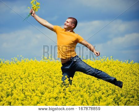 Field of yellow spring flowers, blue sky, young man
