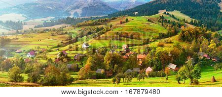 Small village on alpine hills in spring. Spring colors of Alps. Spring panoramic landscape of sunny alpine morning. Country spring background. Beautiful rural scene.