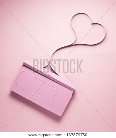 Creative love concept photo of painted VHS cassette with tape in the shape of heart on pink background.