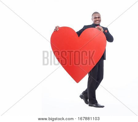 Full lenght portrait of young african man holding big red heart, symbol of love and  Valentine Day. Male wearing in black suite and red tie posing and happy smiling at camera. Isolate on white.
