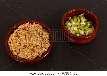 Homemade smoked mackerel pate in a ceramic disk served with sliced scallions on a slate background.