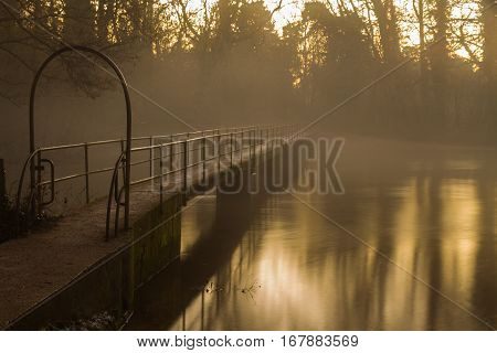 Footbrige At Twilight With Mist.