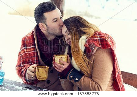 А young couple dressed in coats and scarves drinking a hot drink outdoors