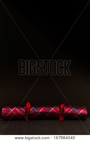 Tartan Christmas cracker with black space above it.