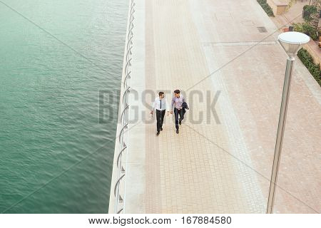 Portrait from above of two businessmen having an outdoor meeting while walking by the river.