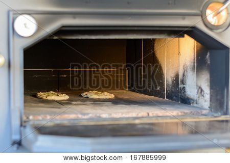 Pizzas in an old oven - close-up view in big open oven