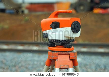 Orange theodolite, geodetic device in the wild, close-up.