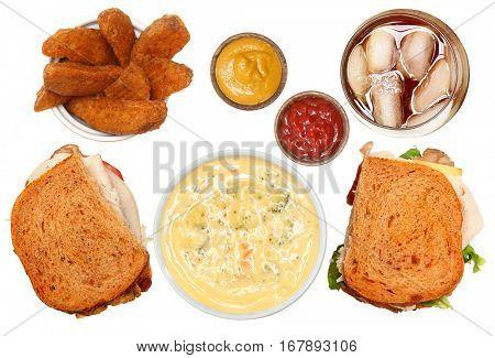 Turkey Club, Broccoli Soup, Potato Wedges and Iced Tea Meal Above Angle Over White