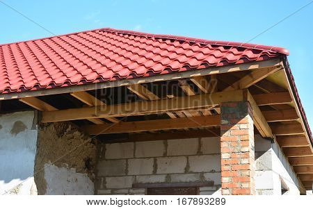 Renovation and repair of old house with new roofing construction exterior. Metal roof installation outdoor.
