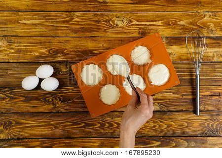 Young girl cooking muffins and putting dough into orange silicon baking form