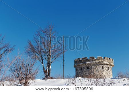 Small ancient fortress covered with snow in winter season. Winter in the mountains. Beautiful winter landscape.