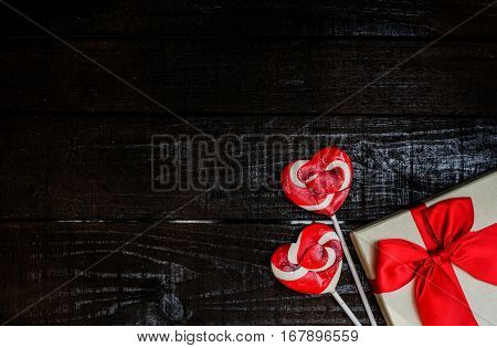 Valentine's day and Sweetest day love concept. Heart shaped candy lollpops and gift box on black wooden boards. Holiday background with copy space.