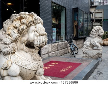Beijing, China - Oct 30, 2016: Guardian twin stone lions from a shop facing outwards to the famous 700-year-old Wangfujing Street.
