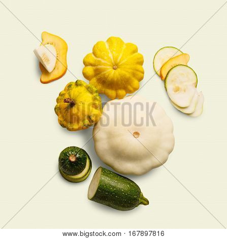 Yellow, white and green zucchini, courgette and round pattipan squashes on white background. Sorts of cucurbit top view