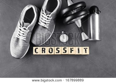 Sport concept. Word CROSSFIT of cubes and training equipment on gray background