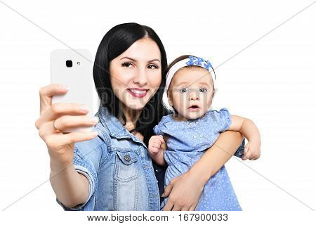 Portrait of a beautiful young mother and her adorable daughter, making selfie on mobile phone, isolated on white background