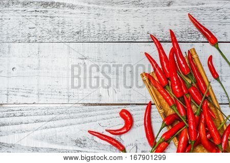 Hot and spicy red chilli peppers on rustic white wood table background. Food background with copy space.