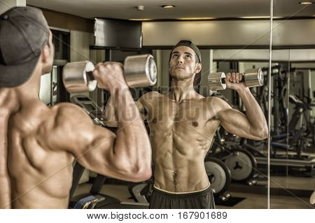 Handsome shirtless muscular young man exercising shoulders in gym with dumbbells