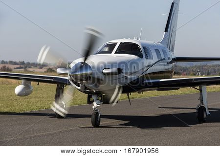 Small private single-engine white piston aircraft on runway. Single-engine piston aircraft taxied on the runway. It has a propeller in motion.