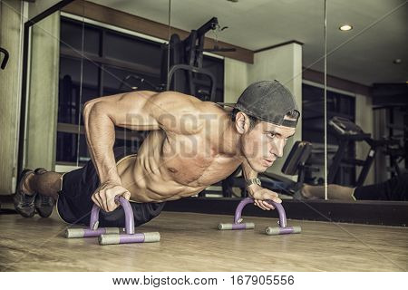 Handsome shirtless muscular young man exercising pecs in gym with push-ups