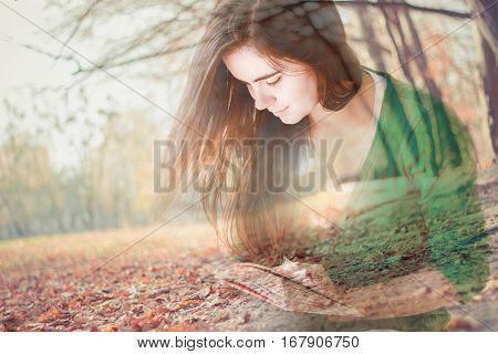 Romantic Double Exposure portrait of beautiful young woman carried away by reading a book in the park