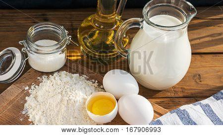 Pancakes Ingredients. Milk Egg Flour Oil Sugar. Wooden Background